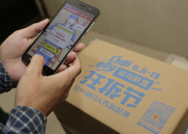 Customer uses his smartphone to scan QR code on the parcel from online shopping